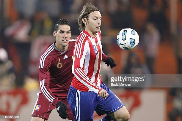 Edgar Barreto of Paraguay struggles for the ball with Gabriel Cichero of Venezuela during a match as part of Copa America 2011 Semifinal at Malvinas...