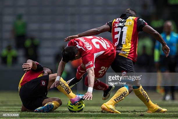 Edgar Benitez of Toluca fights for the ball with Marcelo Alatorre and Jonathan Gonzalez of Leones Negros during a match between Toluca and Leones...