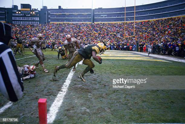 Edgar Bennett of the Green Bay Packers makes a touchdown on the muddy field during the1996 NFC Championship game against the San Francisco 49ers at...