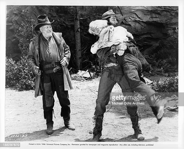 Edgar Buchanan looks on in amusement as Royal Dano grabs Joan Staley in a scene from the film 'Gunpoint' 1966