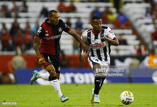 Edgar Castillo of Atlas vies for the ball with Dorlan Pavon of Monterrey during a 2014 Mexican Apertura tournament football match in Guadalajara...