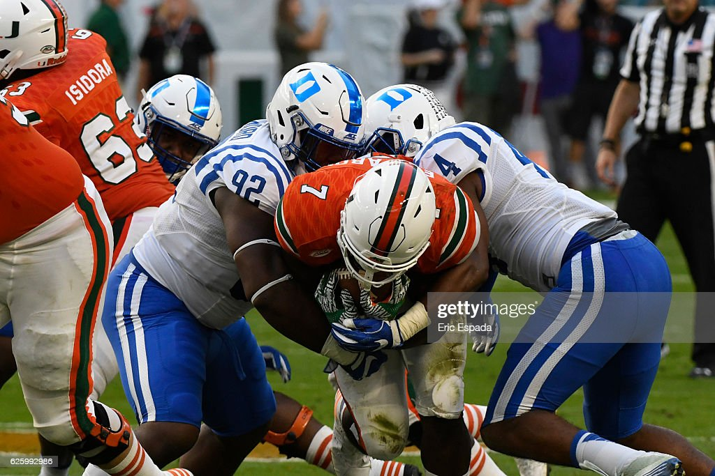 Edgar Cerenord #92 of the Duke Blue Devils and Joe Giles-Harris #44 tackle Gus Edwards #7 of the Miami Hurricanes during the 2nd quarter of the game at Hard Rock Stadium on November 26, 2016 in Miami Gardens, Florida.