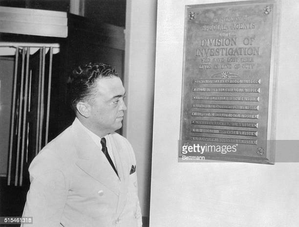 J Edgar Hoover gazes sadly at the bronze plaque which is a grim reminder of the losses incurred by GMen in their relentless war on the underworld...