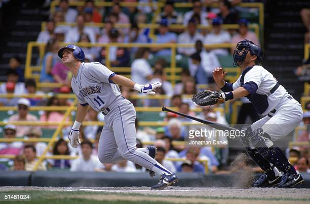 Edgar Martinez of the Seattle Mariners runs out of the batters box as catcher Carlton Fisk of the Chicago White Sox follows the flight of the ball...