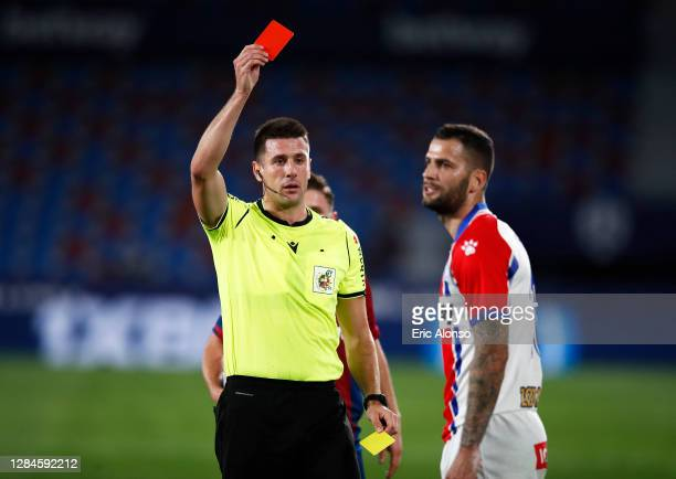 Edgar Mendez of Deportivo Alaves is shown a red card by match referee Isidro Diaz de Mera Escuderos during the La Liga Santander match between...