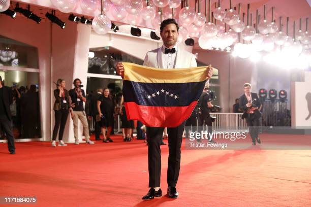 Edgar Ramirez holds the national flag of Venezuela on the red carpet ahead of the Wasp Network screening during the 76th Venice Film Festival at Sala...