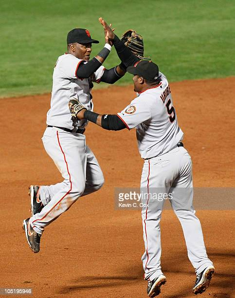 Edgar Renteria and Juan Uribe of the San Francisco Giants celebrate after they defeated the Atlanta Braves 32 during Game Four of the NLDS of the...