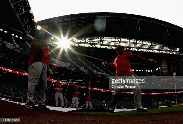 Edgar Renteria and Miguel Cairo of the Cincinnati Reds warm up before the Major League Baseball home opening game against the Arizona Diamondbacks at...