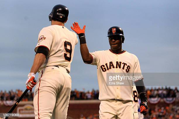 Edgar Renteria of the San Francisco Giants celebrates with Pat Burrell after scoring in the third inning against the Texas Rangers in Game One of the...