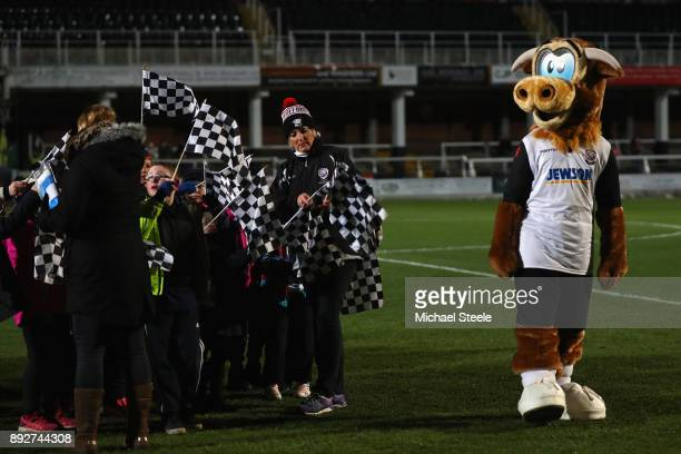 Edgar the Hereford FC Mascot pitchside alongside children with flags ahead of the Emirates FA Cup second round replay match between Hereford FC and...