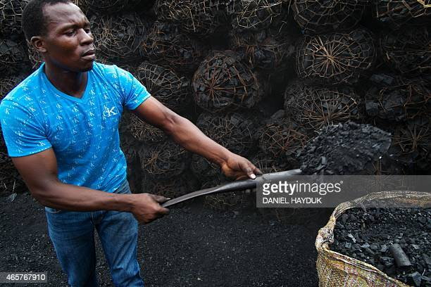 Edgar Zacharia gathers char powder from a charcoal depot in Dar es Salaam on March 10 2015 ARTI Energy is a Tanzanian company providing clean energy...