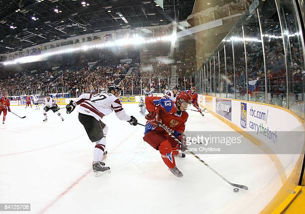 Edgars Lipsbergs of Latvia tries to get the puck from Alexander Komaristy of Russia at the Civic Centre on December 26, 2008 in Ottawa, Ontario,...