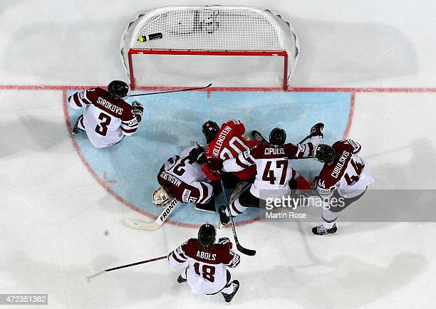Edgars Masalskis goaltender of Latvia makes a save on Denis Hollenstein of Switzerland during the IIHF World Championship group A match between...