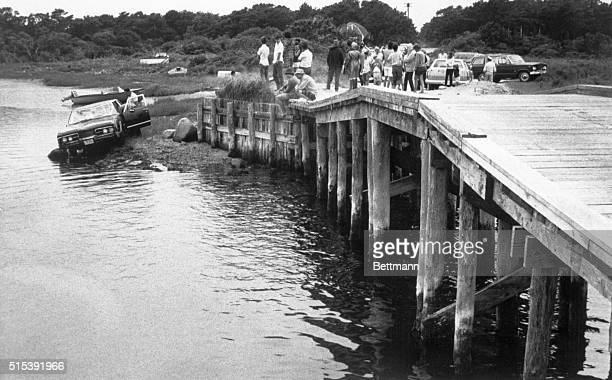 7/24/1969 Edgartown MA Curious spectators look on from pier at the car driven by Massachusetts Senator Edward Kennedy which plunged off a bridge on...