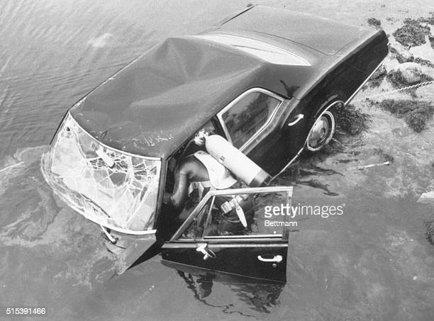 Edgartown Massachusetts A frogman attempts to raise car eight hours after it plunged into pond here with Massachusetts Senator Edward Kennedy behind...