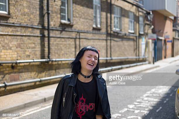 edgy woman laughing on the city streets - giacca di pelle foto e immagini stock