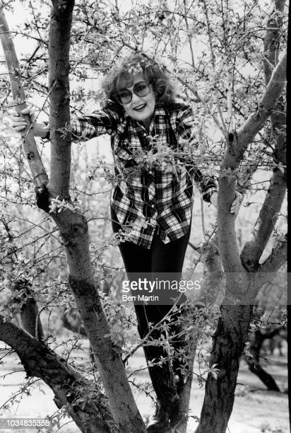 Edie Adams comedienne and singer climbing an almond tree on her almond ranch in Bakersfield March 26 1982
