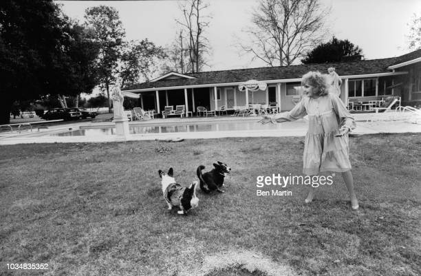 Edie Adams comedienne and singer playing with her dogs in front of her home on an almond ranch in Bakersfield March 26th 1982