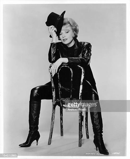 Edie Adams tips her hat as she sits in a chair in a publicity portrait for the film 'Made In Paris' 1966