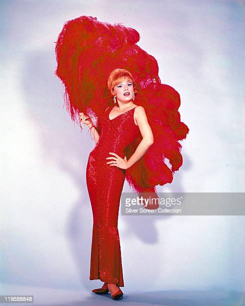 Edie Adams US singer actress and comedienne wearing a long red sleeveless dress holding a large feather fan in a studio portrait against a white...