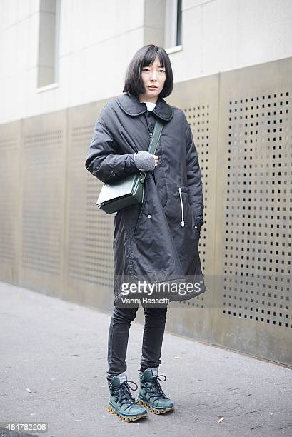 Edie Fu poses wearing a Comme des Garcons coat Anteprima bag and Camper shoes on February 28 2015 in Milan Italy