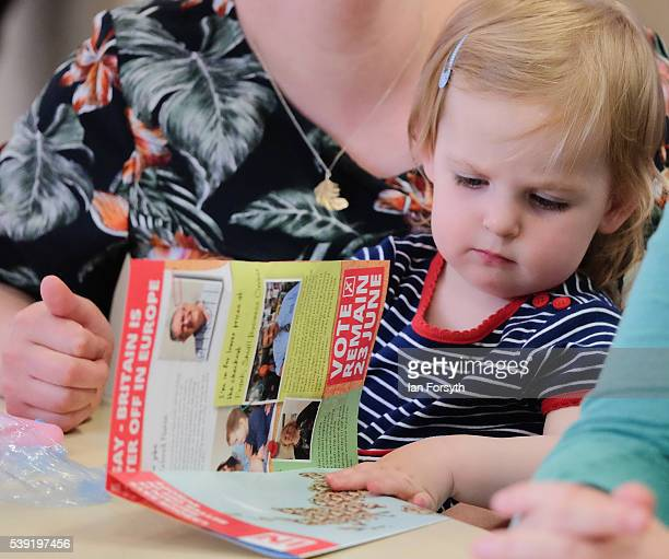 Edie Rowell from Sunderland plays with campaign literature as Labour's Shadow Cabinet Minister Gloria de Piero speaks with a group of women voters to...