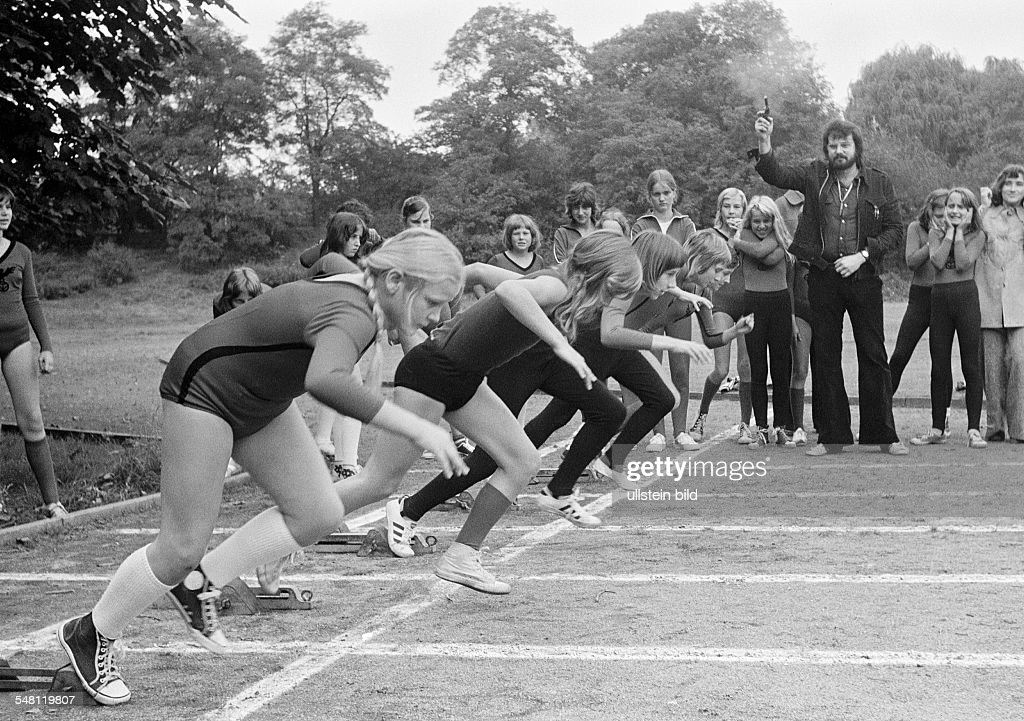 edification, school, sports, physical education, gym class, track racing, sprint, start, young girls starting, aged 10 to 12 years, sports teacher gives the starting signal by a starting pistol - 21.09.1974 : News Photo