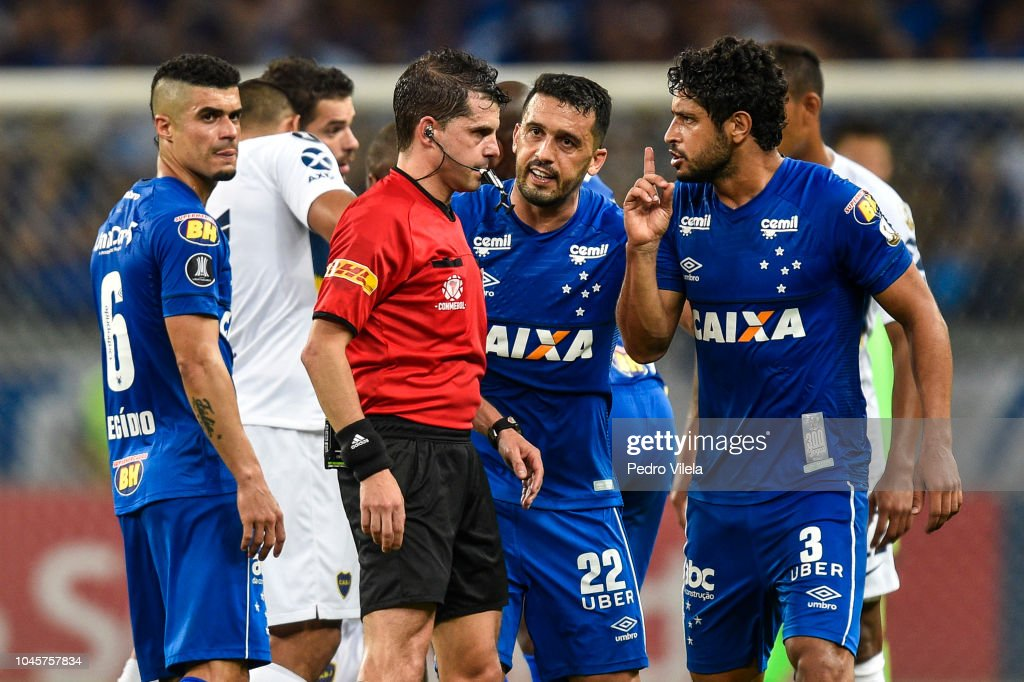 Edilson and Leo of Cruzeiro argue with referee Andres Cunha during