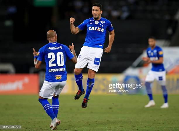 Edilson celebrates with teammate Bruno Silva of Cruzeiro after scoring the equalizer during a match between Botafogo and Cruzeiro as part of...