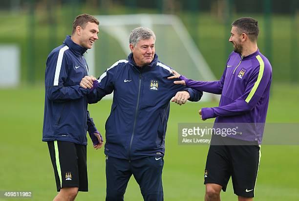 Edin Dzeko and Aleksandar Kolarov of Manchester City joke around with Brian Kidd the assistant manager of Manchester City during a training session...
