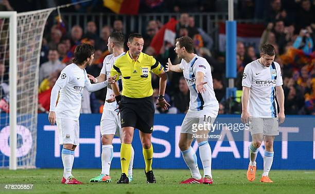 Edin Dzeko and David Silva of Manchester City argue with referee Stephane Lannoy after conceding the opening goal during the UEFA Champions League...