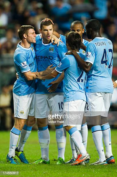 Edin Dzeko is congratulated by teammates after scoring the winning goal during the Barclays Asia Trophy Final match between Manchester City and...