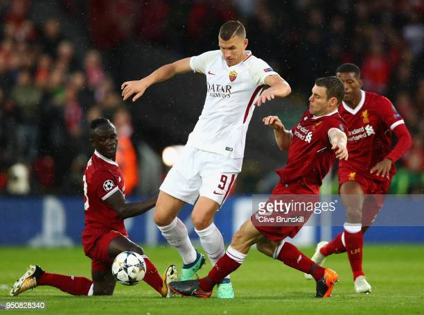 Edin Dzeko of AS Roma battles with Sadio Mane and James Milner of Liverpool during the UEFA Champions League Semi Final First Leg match between...