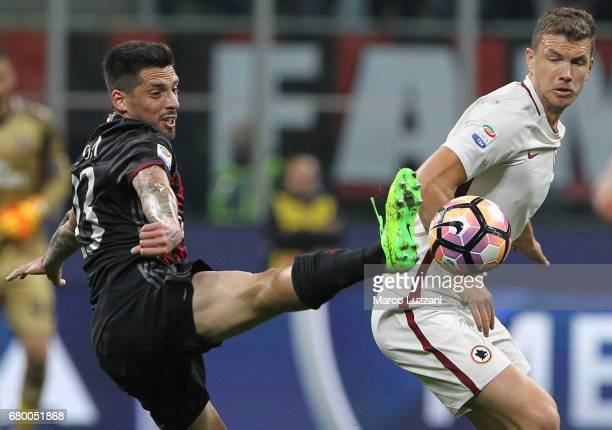 Edin Dzeko of AS Roma competes for the ball with Jose Sosa of AC Milan during the Serie A match between AC Milan and AS Roma at Stadio Giuseppe...