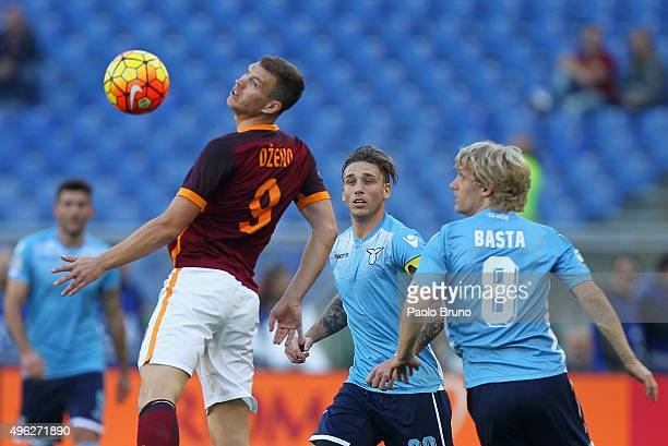 Edin Dzeko of AS Roma competes for the ball with Luca Biglia and Dusan Basta of SS Lazio during the Serie A match between AS Roma and SS Lazio at...