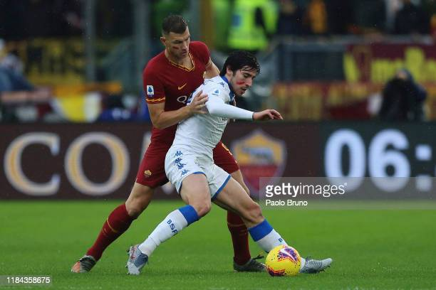 Edin Dzeko of AS Roma competes for the ball with Sandro Tonali of Brescia Calcio during the Serie A match between AS Roma and Brescia Calcio at...