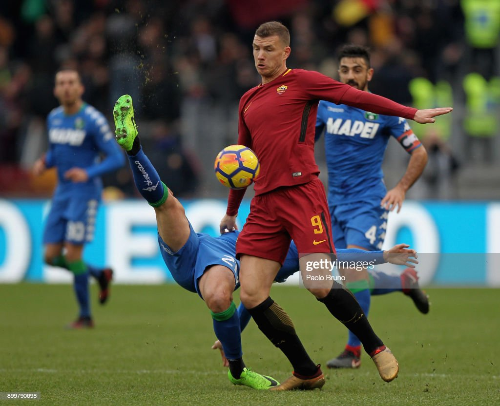 Edin Dzeko of AS Roma competes with Paolo Cannavaro of US Sassuolo during the serie A match between AS Roma and US Sassuolo at Stadio Olimpico on December 30, 2017 in Rome, Italy.