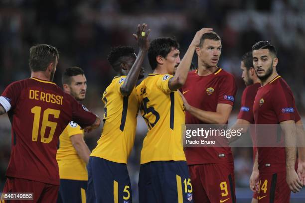 Edin Dzeko of AS Roma competes with Thomas and Stefan Savic of Atletico Madrid during the UEFA Champions League group C match between AS Roma and...