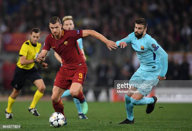 Edin Dzeko of AS Roma is challenged by Gerard Pique of Barcelona during the UEFA Champions League Quarter Final Second Leg match between AS Roma and...