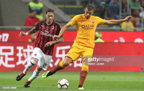 Edin Dzeko of AS Roma is challenged by Lucas Biglia of AC Milan during the serie A match between AC Milan and AS Roma at Stadio Giuseppe Meazza on...