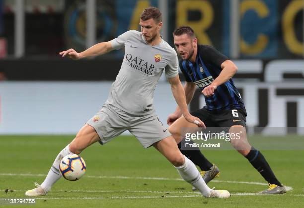 Edin Dzeko of AS Roma is challenged by Milan Skriniar of FC Internazionale during the Serie A match between FC Internazionale and AS Roma at Stadio...