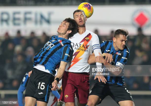 Edin Dzeko of AS Roma jumps for the ball against Marten De Roon and Rafael Toloi of Atalanta BC during the Serie A match between Atalanta BC and AS...