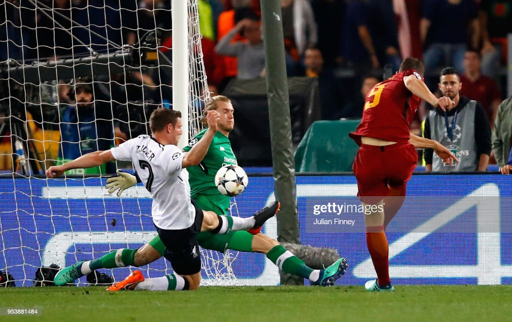 Edin Dzeko of AS Roma scores his sides second goal under pressure from James Milner and Loris Karius of Liverpool during the UEFA Champions League Semi Final Second Leg match between A.S. Roma and Liverpool at Stadio Olimpico on May 2, 2018 in Rome, Italy.