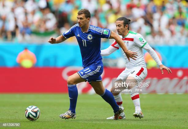 Edin Dzeko of Bosnia and Herzegovina and Andranik Teymourian of Iran compete for the ball during the 2014 FIFA World Cup Brazil Group F match between...