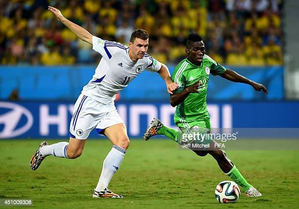 Edin Dzeko of Bosnia and Herzegovina and Kenneth Omeruo of Nigeria compete for the ball during the 2014 FIFA World Cup Brazil Group F match between...