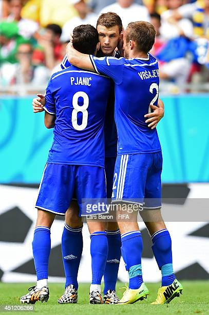 Edin Dzeko of Bosnia and Herzegovina celebrates scoring his team's first goal with his teammates Miralem Pjanic and Avdija Vrsajevic during the 2014...