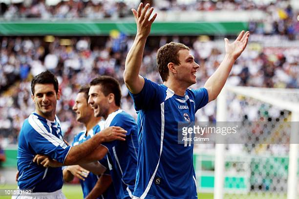 Edin Dzeko of BosniaHerzegovina celebrates after scoring his team's first goal with team mates during the international friendly match between...