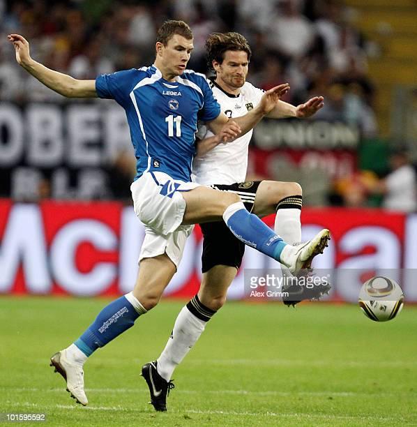Edin Dzeko of Bosnia-Herzegovina is challenged by Arne Friedrich of Germany during the international friendly match between Germany and...