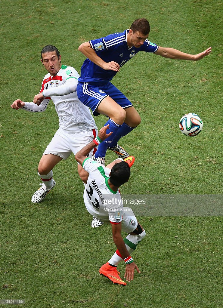 Edin Dzeko of Bosnia-Herzegovina leaps above Mehrdad Pooladi and Andaranik Timotian of Iran during the 2014 FIFA World Cup Brazil Group F match between Bosnia-Herzegovina and Iran at Arena Fonte Nova on June 25, 2014 in Salvador, Brazil.