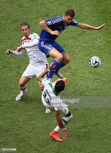 Edin Dzeko of BosniaHerzegovina leaps above Mehrdad Pooladi and Andaranik Timotian of Iran during the 2014 FIFA World Cup Brazil Group F match...